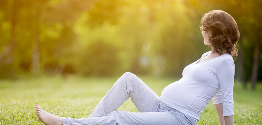Happy pregnant woman on late pregnancy stage sitting on grass la