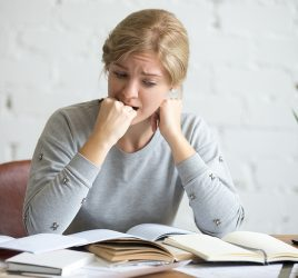 Portrait of a student girl sitting at the desk biting her fist